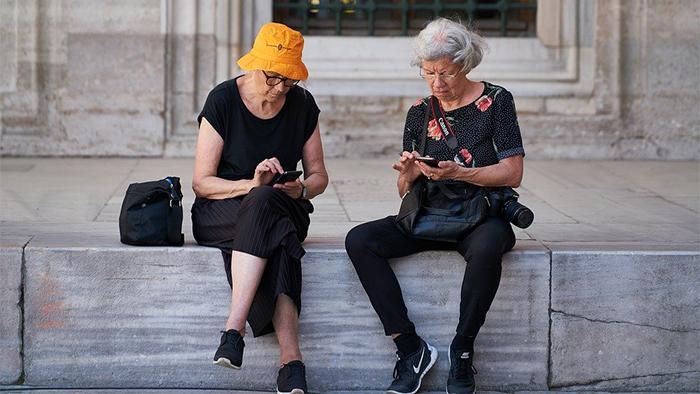 Deux femmes agées assises à l'extérieur d'un monument