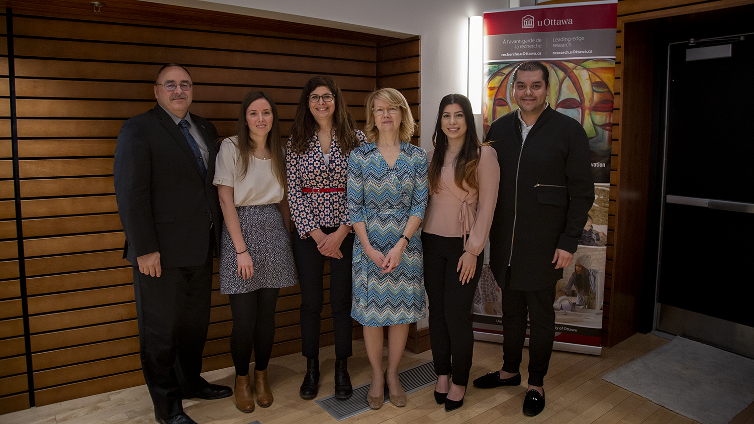 A group of six people standing in front of a uOttawa Research banner