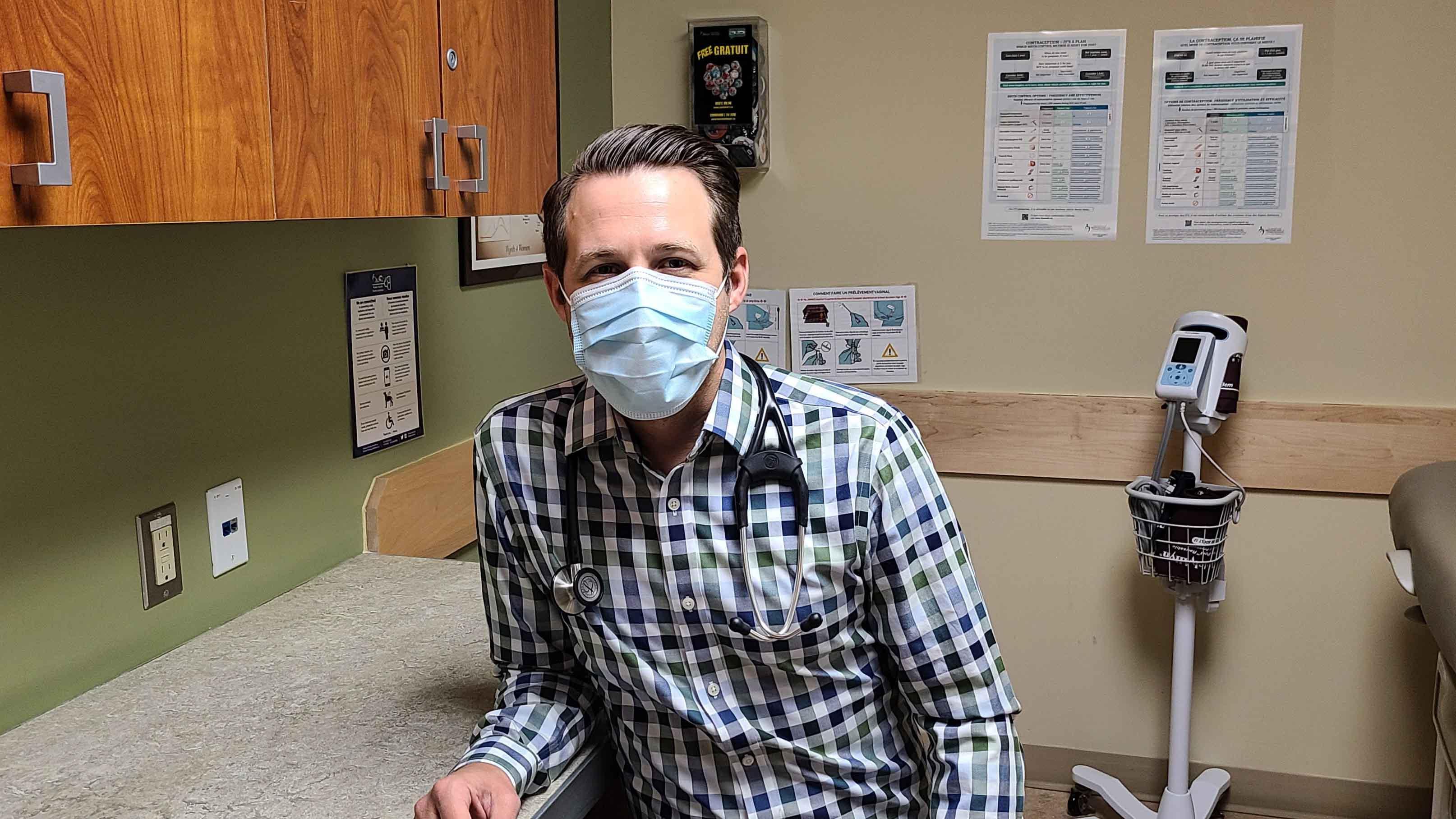 Un infirmier portant un masque est assis dans une clinique.