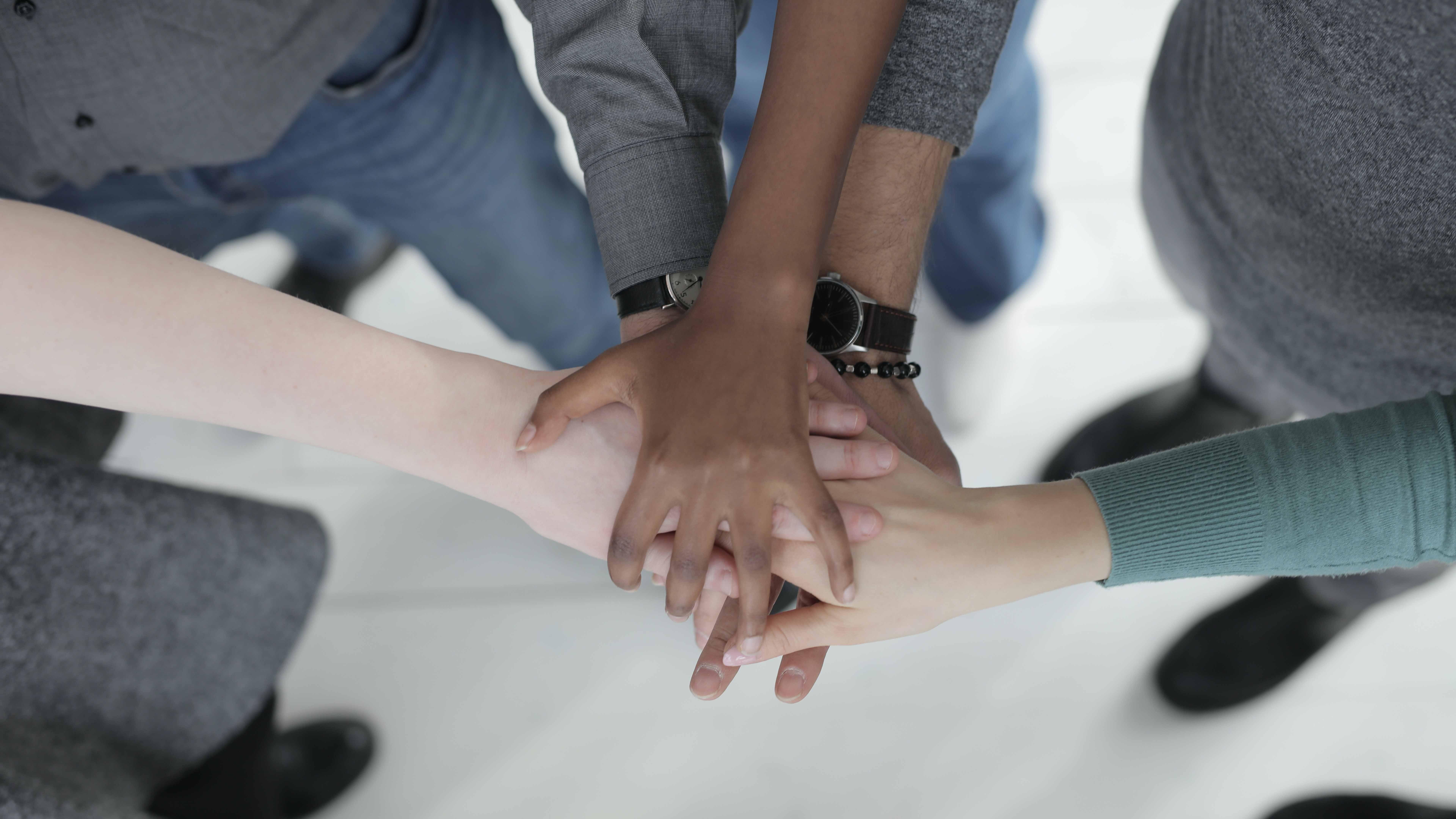 Des collègues méconnaissables qui joignent leurs mains