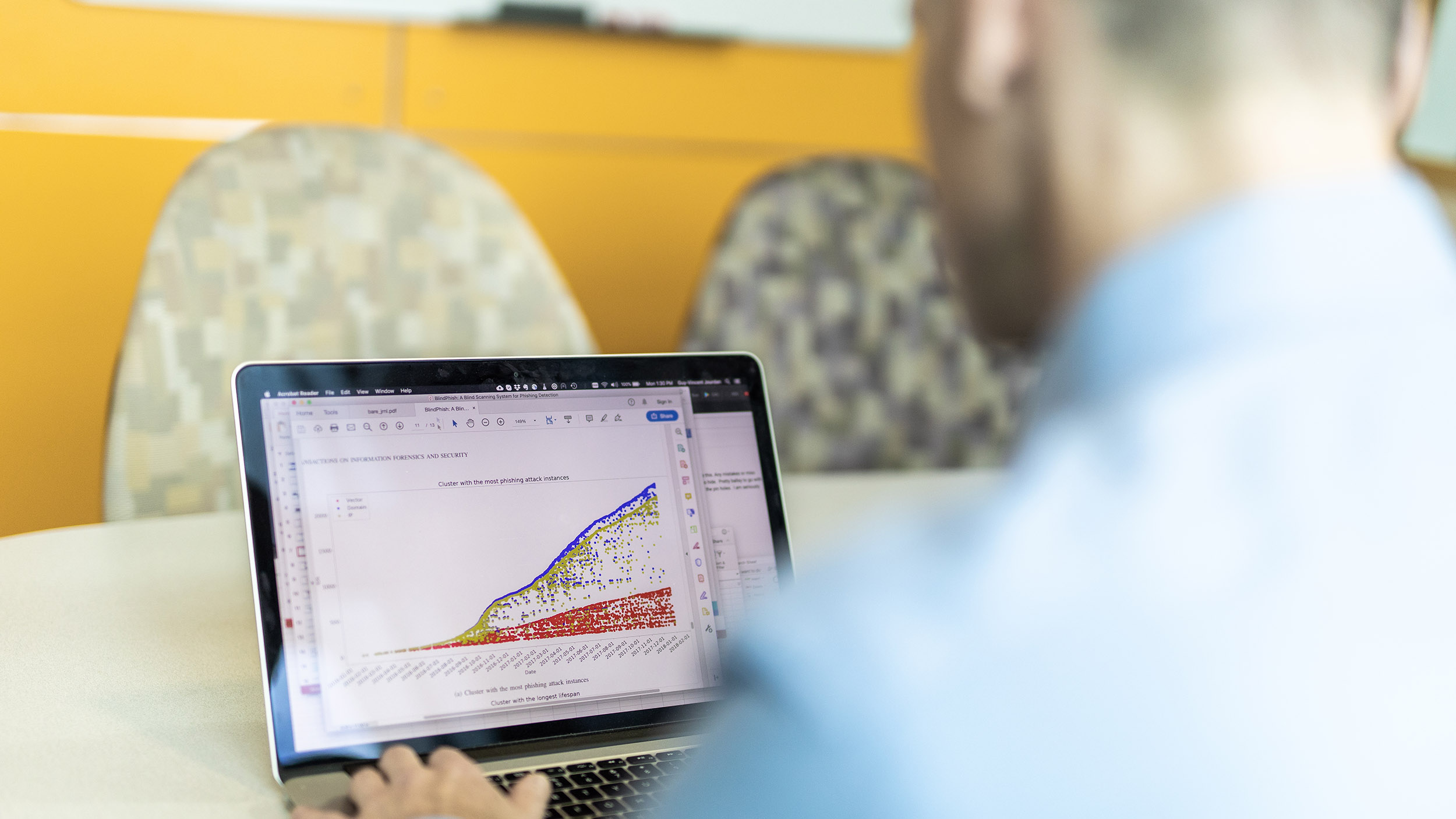 A man looks at a graph presenting data related to cybercrime on a laptop computer.