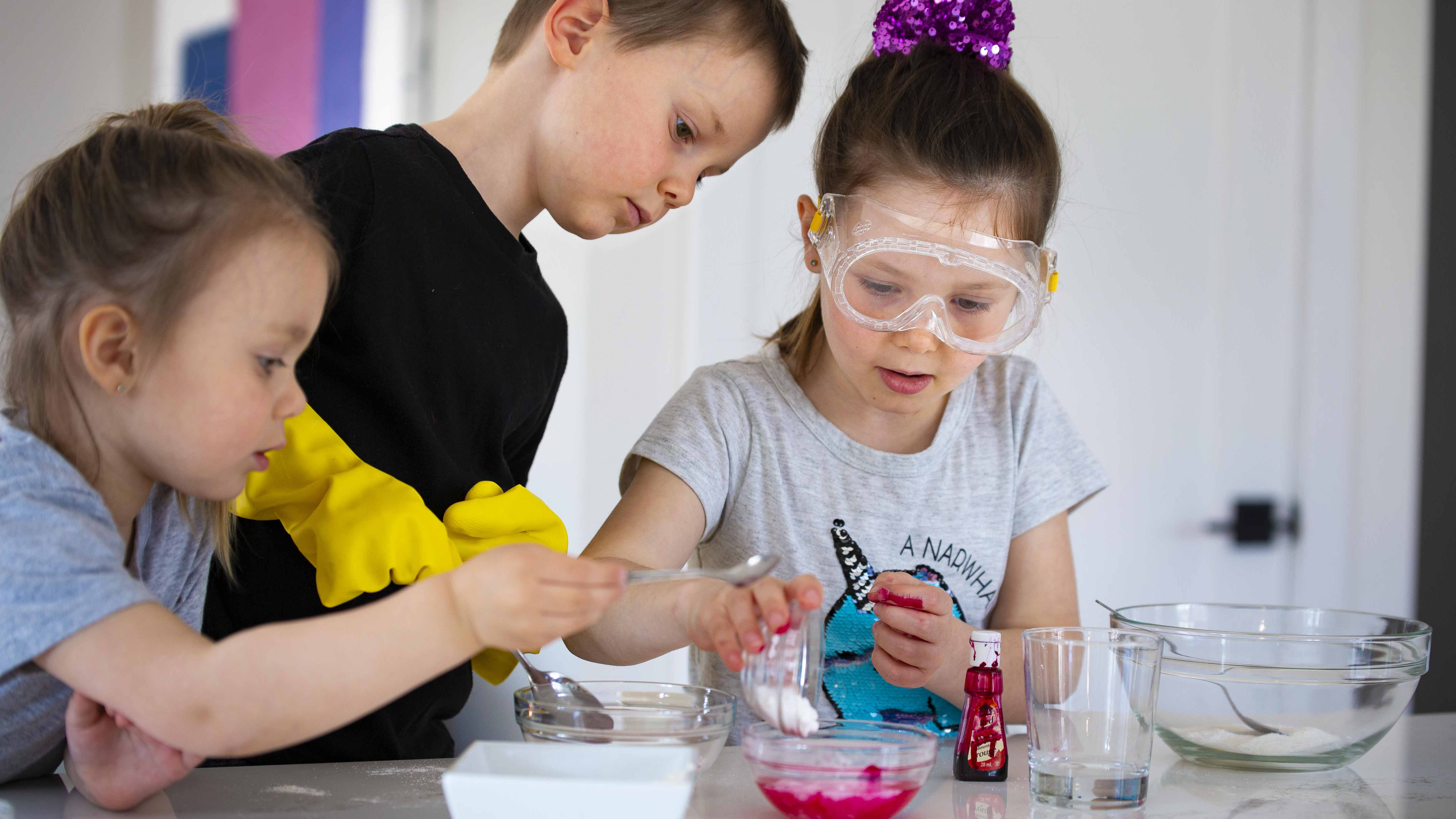 Three young kids doing scientific experiences