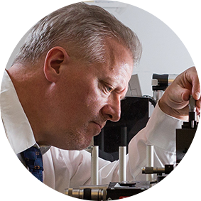 Professor looking at microscope
