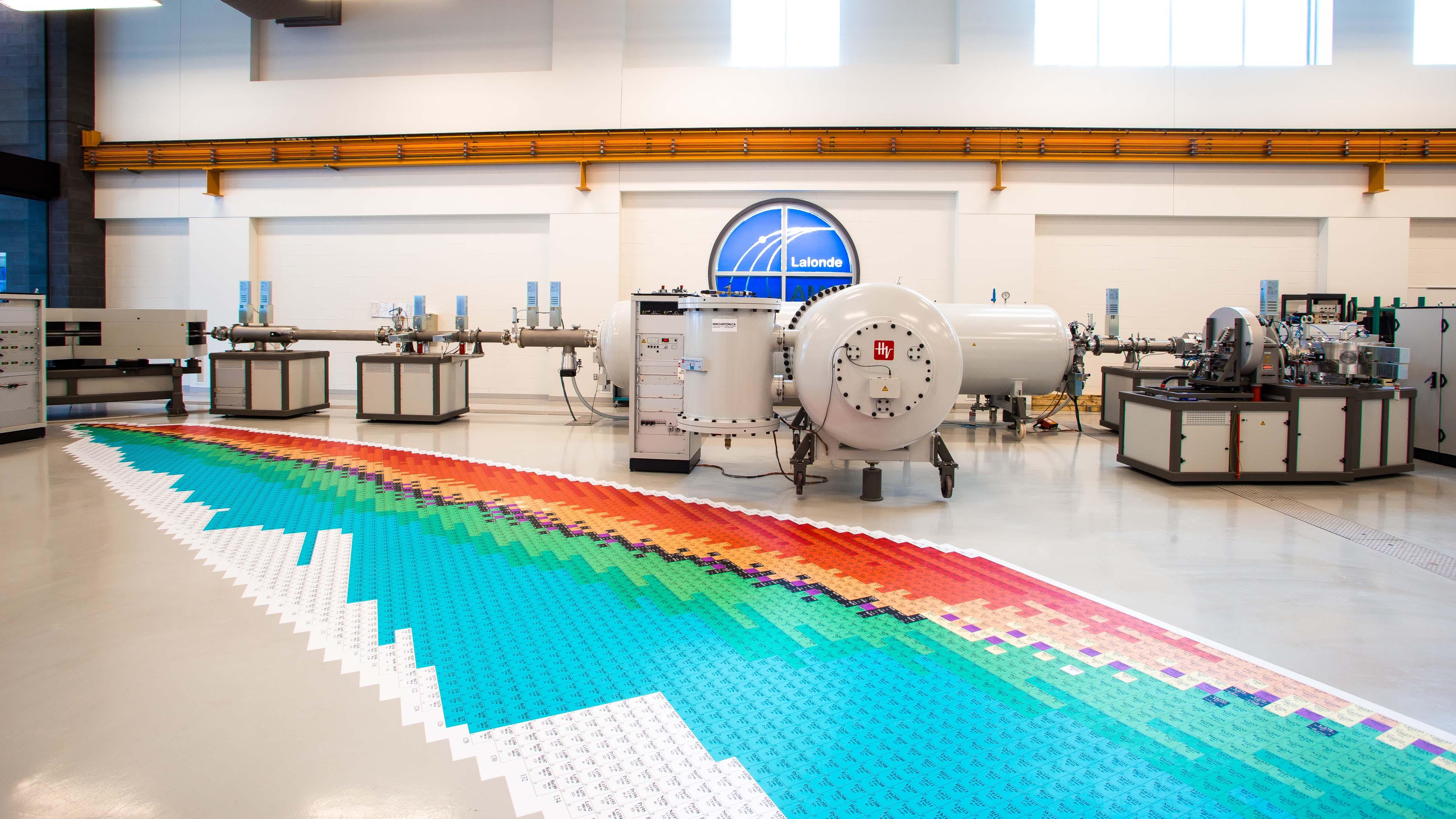 Intérieur d'un laboratoire montrant un spectromètre de masse par accélérateur et un gigantesque tableau périodique imprimé au sol