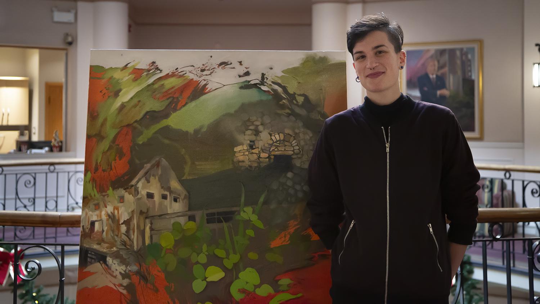 Nic Cooper standing beside her painting