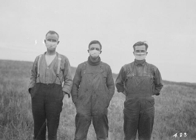 Three 1918 men are wearing masks in a field.