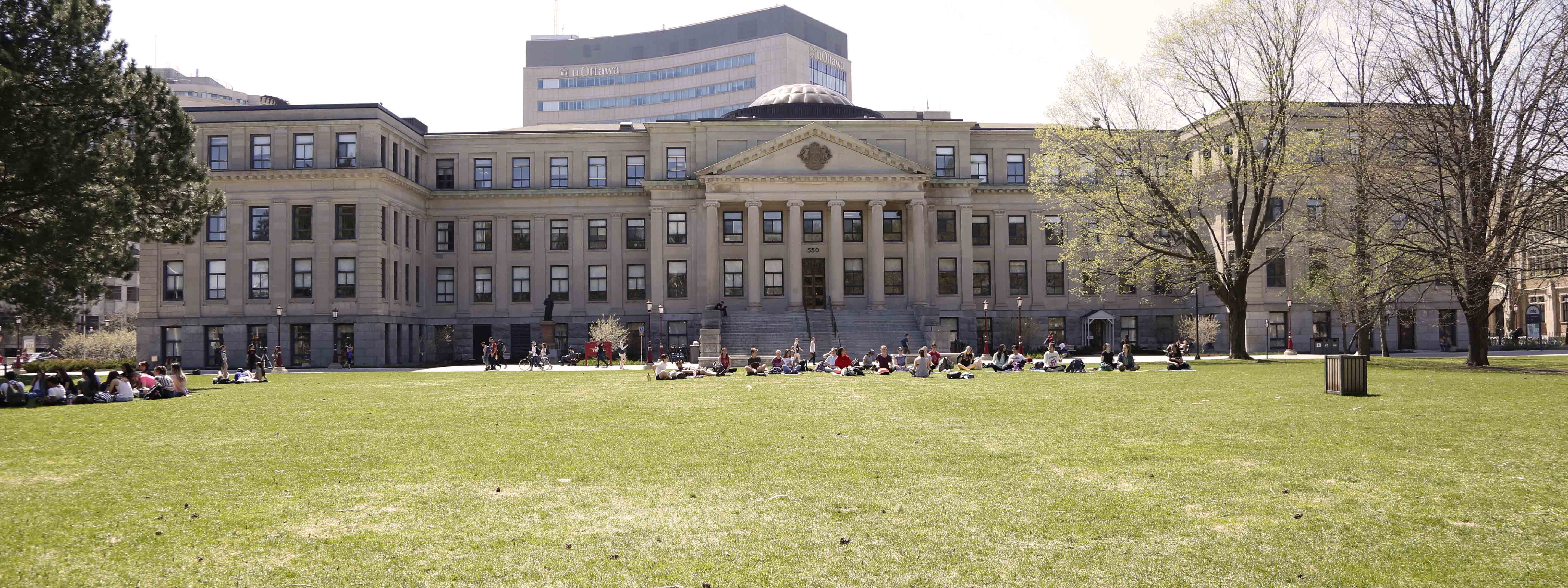 Photo of Tabaret building with students practicing yoga on the lawn in front of the large columns, while a group of people are sitting in a circle on the left side of the photo.