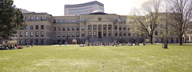 Photo de l'édifice Tabaret et de ses colonnes, devant lesquelles des étudiants pratiquent le yoga, alors que d'autres étudiants sont assis en cercle à la gauche sur la pelouse .