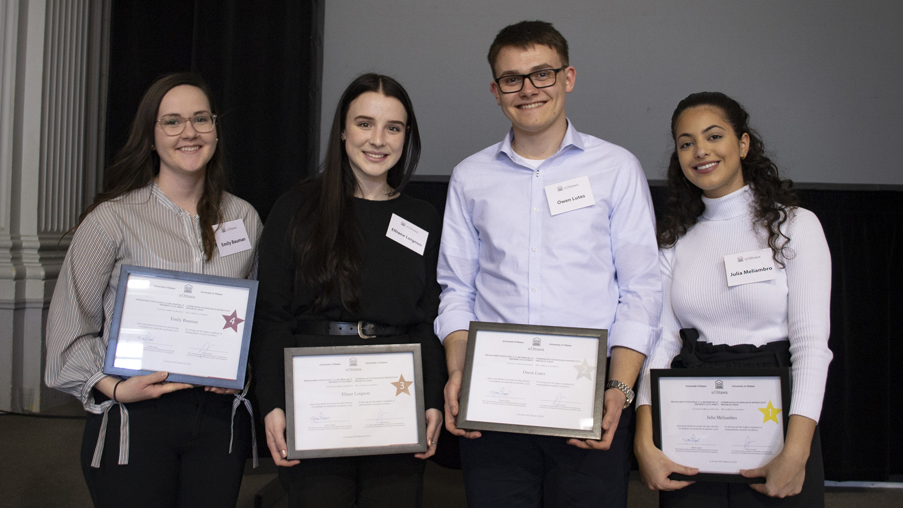 Four students standing side by side with a certificate in their hands