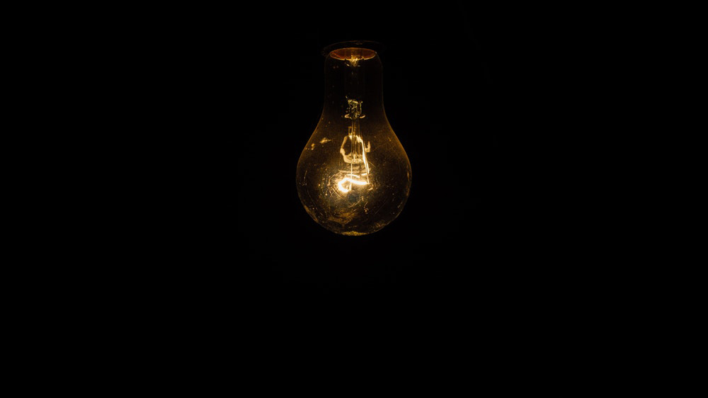 A yellow light bulb on a black background