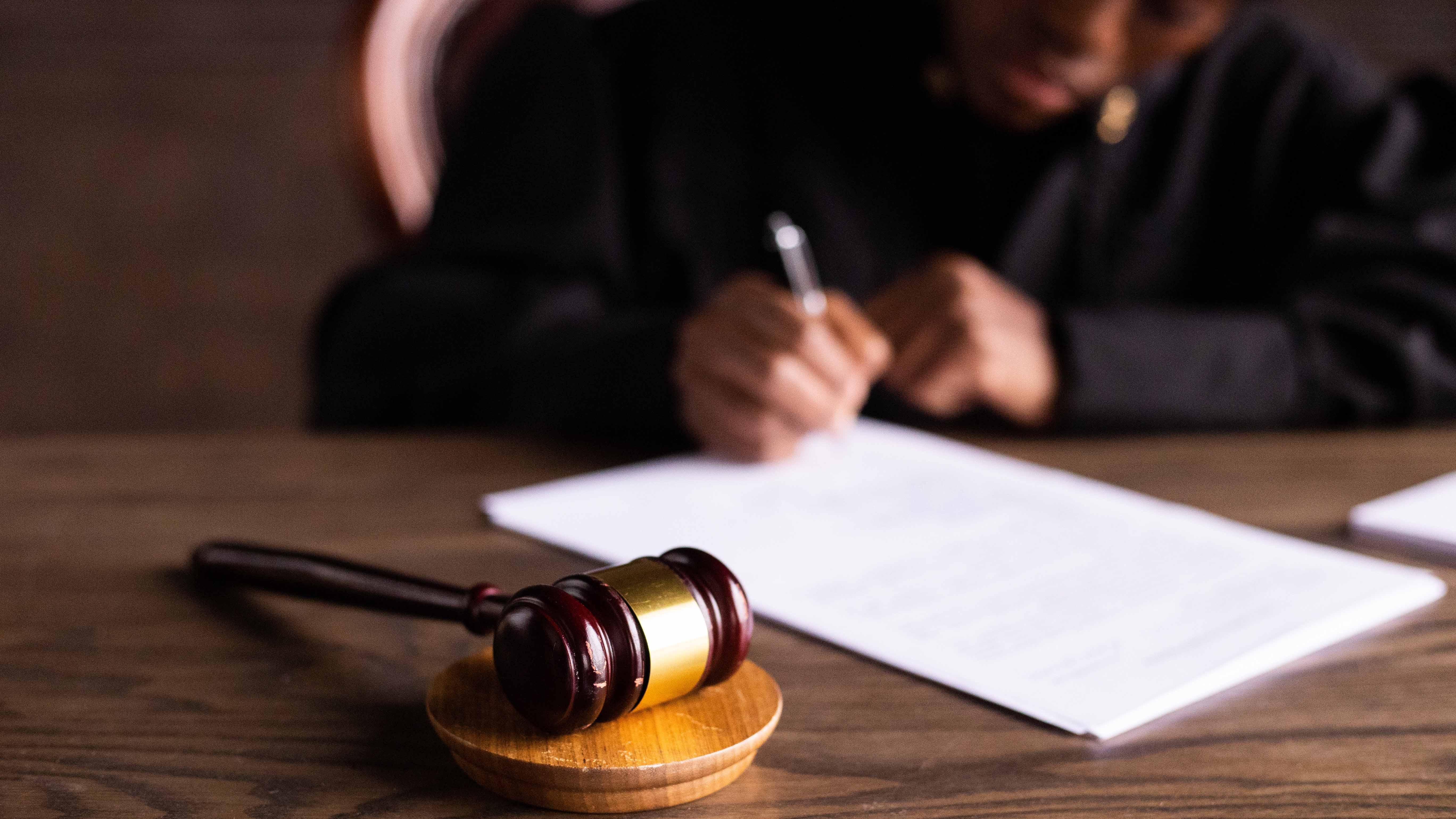 Un marteau du président est placée devant une personne juge