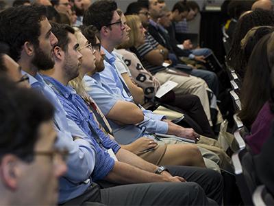 Une rangée de personnes assises dans une salle de conférence