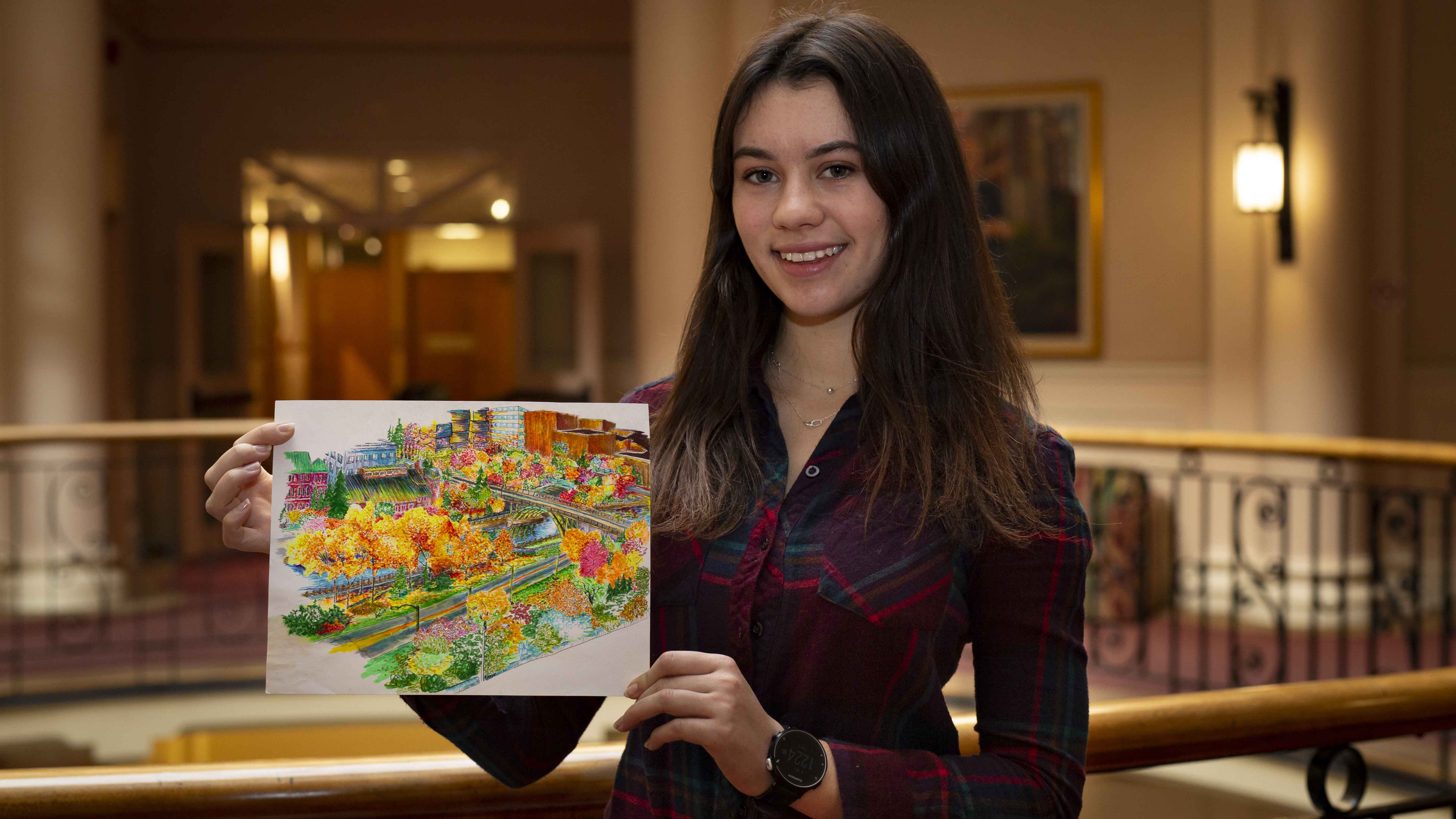 Kira F. Robinson holding her artwork made of highlighters and pens.