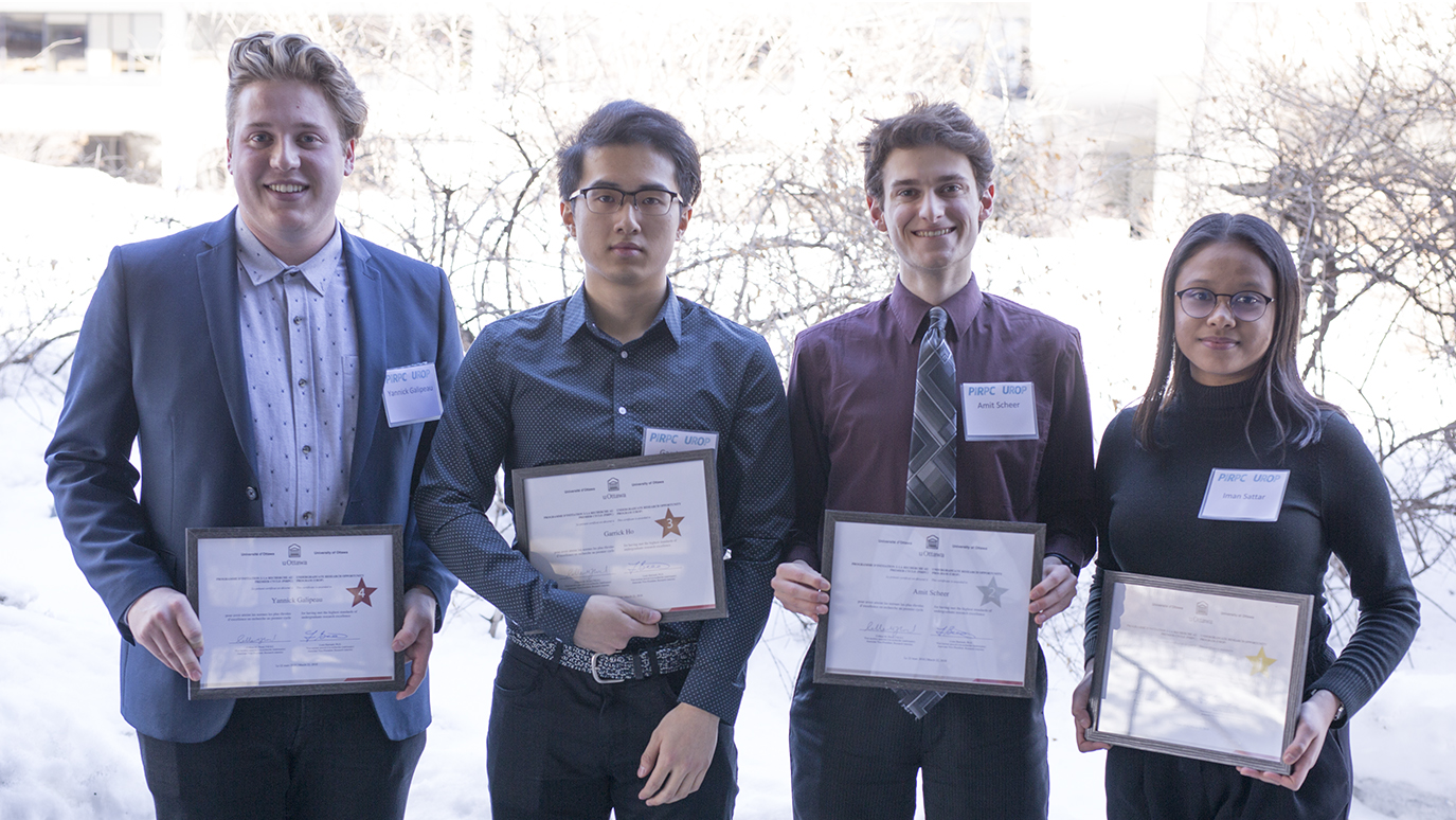 Four students are standing side by side while holding a certificate in their hands.
