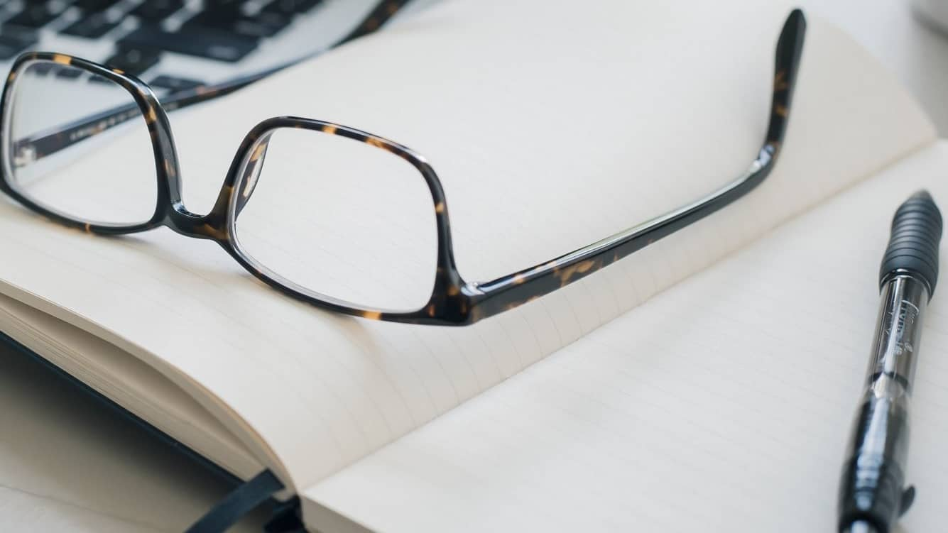 A pair of glasses is sitting beside a pen on an opened notebook.