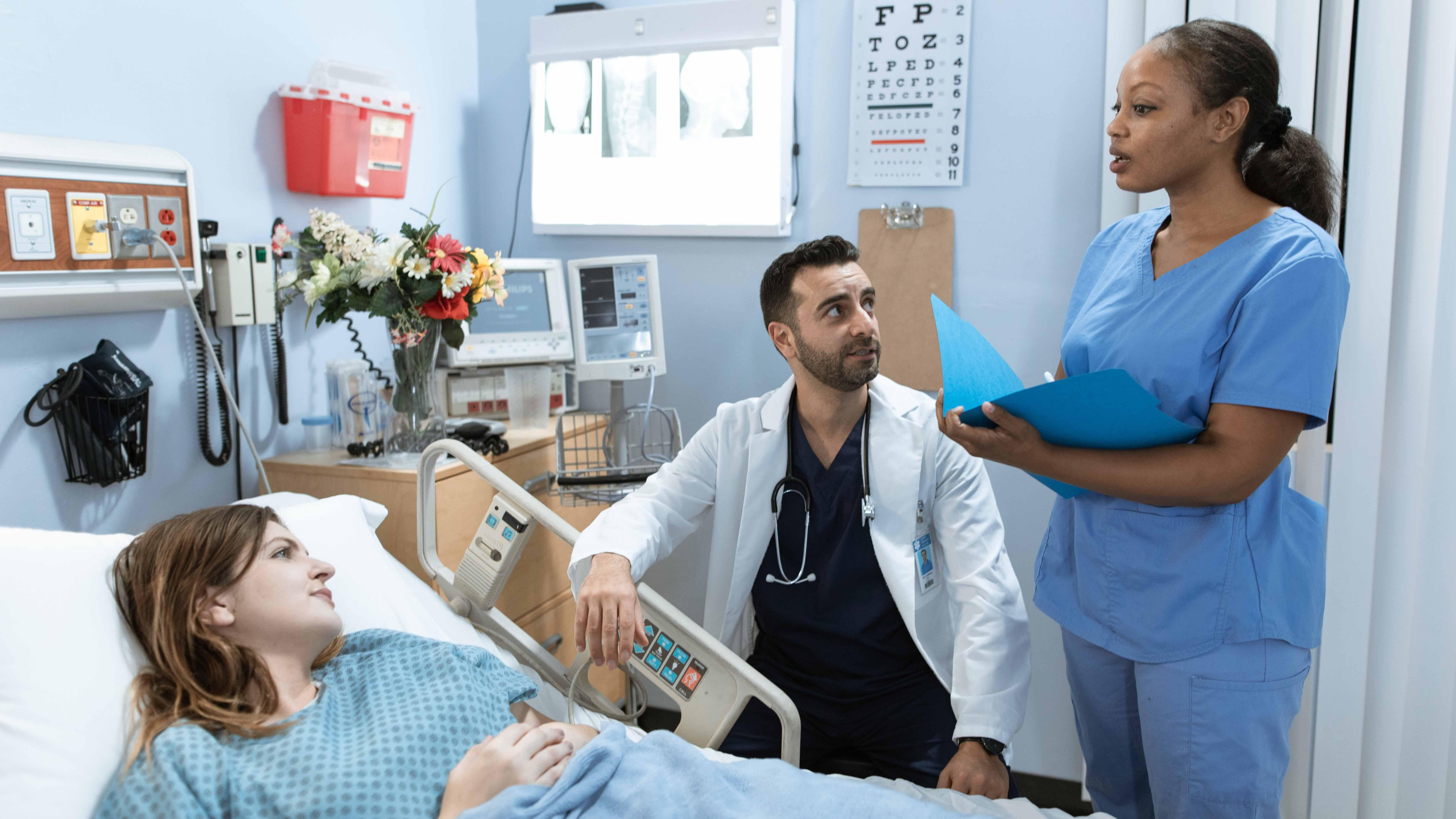 Une salle d'hopital comprenant une patiente sur le lit, un infirmière debout et un médecin assis.