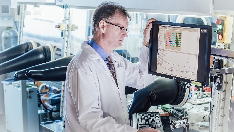 Le professeur Michael Organ est dans un laboratoire et regarde des données scientifiques, debout devant un ordinateur.