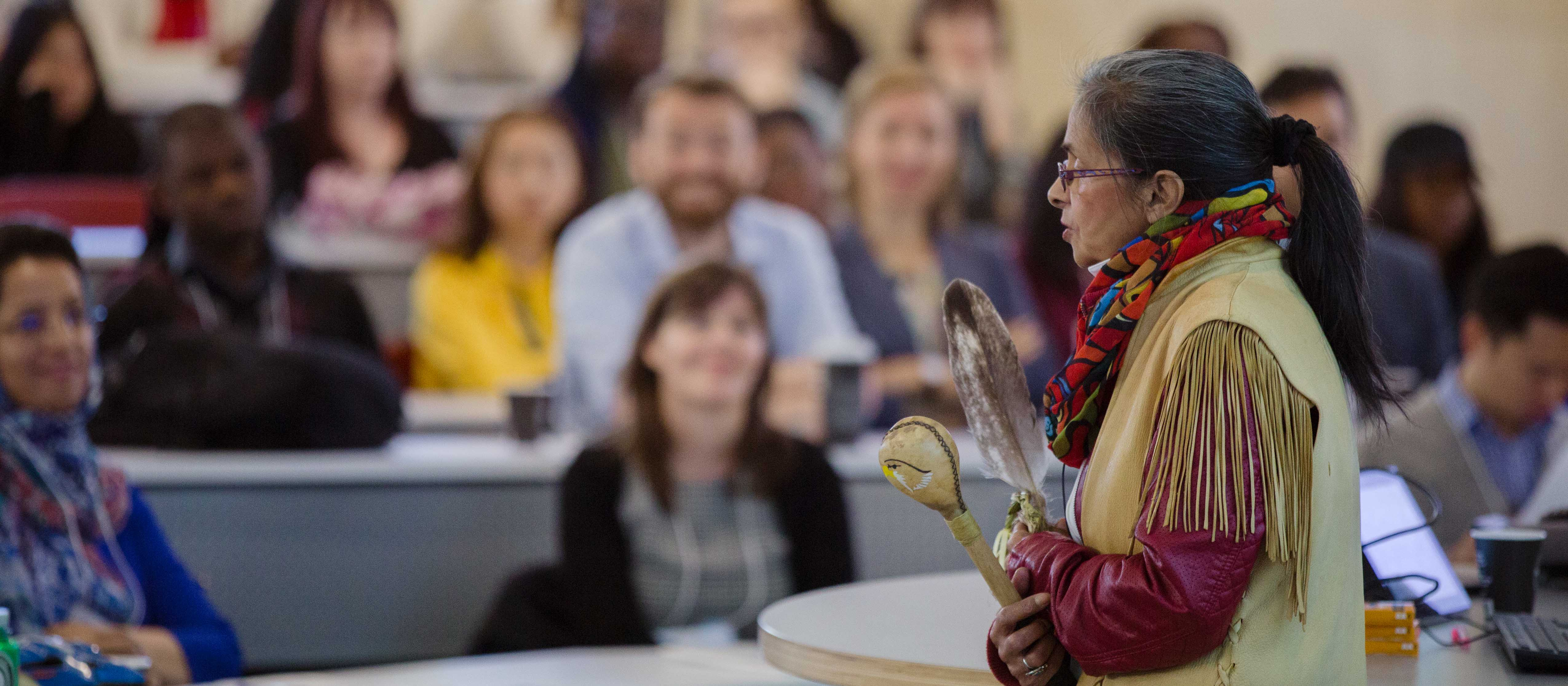 An indigenous woman speaking in front of a class